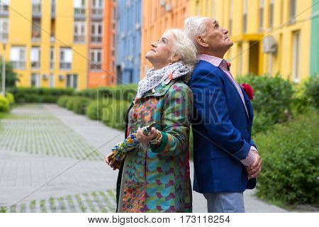 Elegantly dressed old man and an old woman standing back to back in the open air near the multi-colored apartment blocks