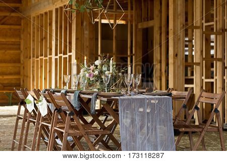 Wedding party in a wooden barn. Candles and bouquet. Vintage Style.