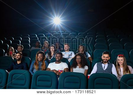 Big screen nights. Shot of young people sitting in the cinema hall enjoying the movie on a big screen