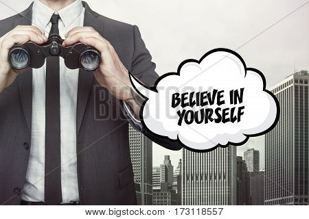 Believe in yourself text on  blackboard with businessman and key