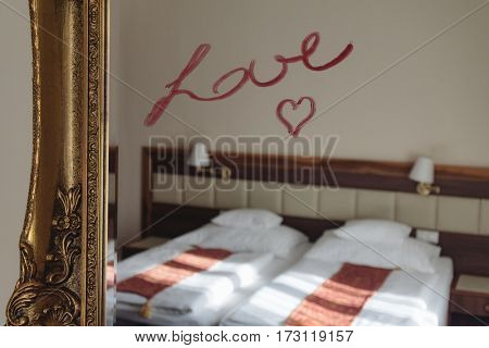 Hotel room, mirror with rouge love text
