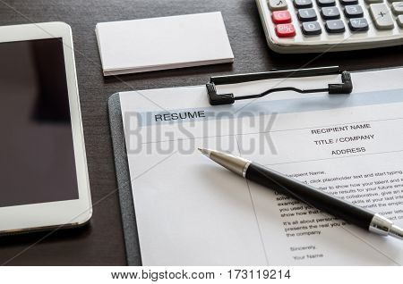 Close-up Resume, Pen, Digital Tablet, Calculator And Business Card On Wooden Desk.