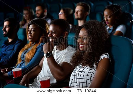 Our weekend tradition. Young happy people smiling joyfully while watching a movie together at the local movie theatre