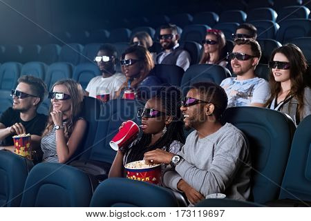 Entertainment snack. Young African man eating popcorn while watching a 3D movie his girlfriend sipping her drink at the cinema