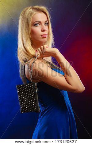Fashion elegant evening outfit. Stylish woman fashionable blonde girl holding black rivet leather handbag bag in night club dancing.
