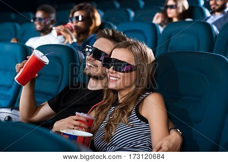 3D love. Gorgeous young couple in love hugging while enjoying a 3D movie at the local movie theatre