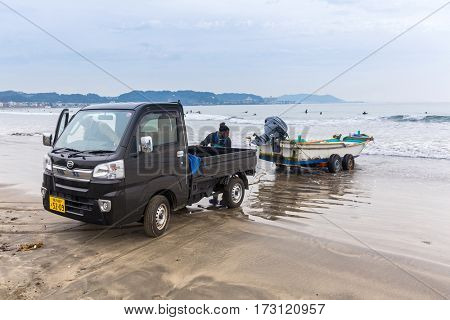 KAMAKURA, JAPAN - NOVEMBER 10, 2016: Fisherman boat and car on the Pacific beach of Kamakura, Japan. Kamakura is a city in Kanagawa Prefecture, about 50 kilometres south-west of Tokyo.