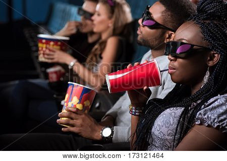 Sipping her drink. Closeup portrait of an attractive African woman sipping her coke while enjoying a movie at the cinema with her handsome man