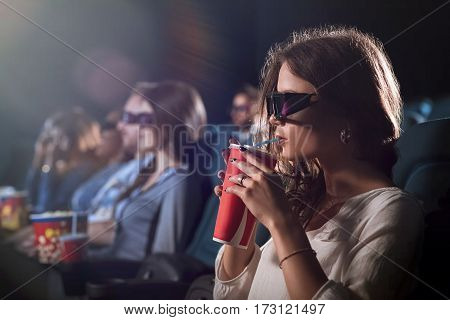 Movie mania. Shot of a beautiful young female in 3D glasses sipping her drink while watching a movie at the cinema