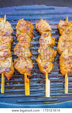 pan fried round steak cubes on sticks on a grill pan