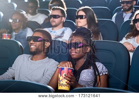 Ready to be entertained.Portrait of an attractive African couple sipping enjoying a 3D movie at the cinema