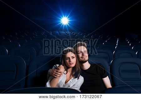 So cozy together. Portrait of a young couple in love having a date at the cinema watching a movie in an empty cinema hall