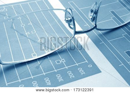 Glasses on charts with different data. Audit report concept.