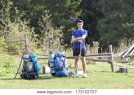 Hiker with a backpack standing in mountains relaxing and enjoying valley view