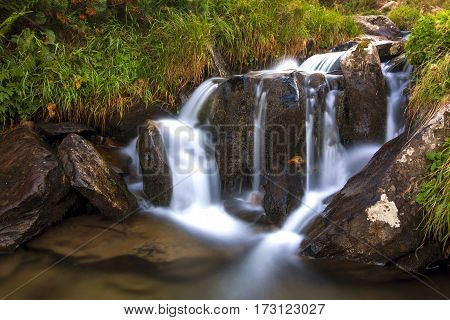 Beautiful Little Waterfall In Mountains With White Foamy Water