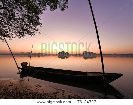 Long tail boat on a river side and tree leaves in front of an amazing colorful orange blue yellow calm and tranquil sunset without direct sunlight