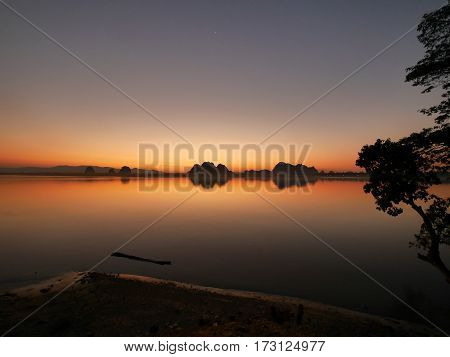 Intense orange sunset over river with reflection and river side in front