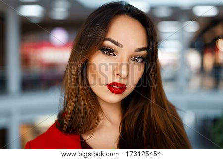 Stylish Portrait Of A Young Woman With Red Lips On A Background Of The Shopping Center