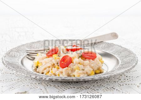 Creamy corn basil and tomato risotto on a silver plate.