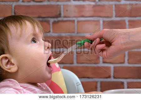 Mommy feeds the baby from the spoon porridge