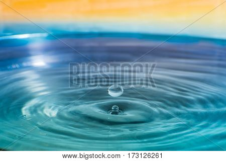 Water drop falling into water making a concentric circles