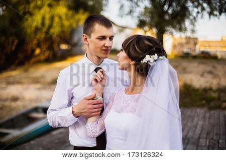 Groom and bride in white dress on background of water. Wedding photography. A happy family