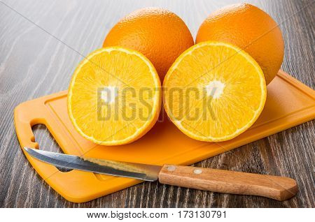 Half And Whole Ripe Oranges, Kitchen Knife On Cutting Board