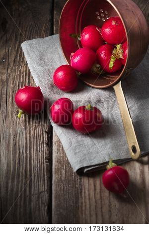 Red radishes in a colander on a wooden table vertical