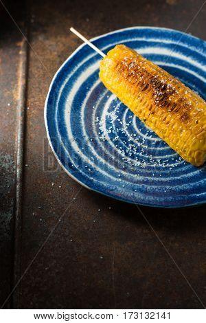 Roasted corn with salt on blue ceramic plate vertical