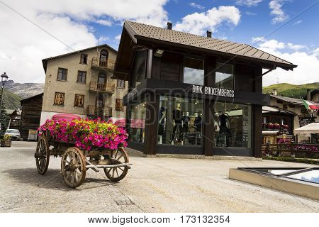 Livigno, Italy - August 1: Wain With Flowers In Front Of Fashion Shops On Streets Of Duty-free Area