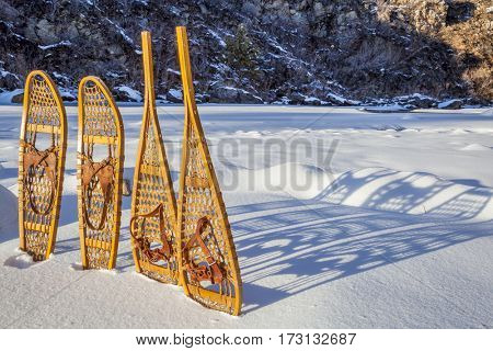vintage wooden Huron and Bear Paw snowshoes with leather binding in snow with shadow