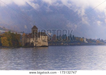 CHILLON CASTLE, SWITZERLAND - NOVEMBER 06, 2014: Chillon Castle, one of the most visited castles in Switzerland and Europe, is in the hazy, cloudy midday.