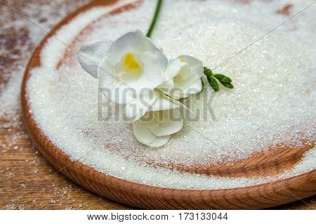 sugar white freesia flower on wooden tray
