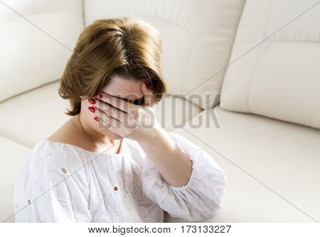 Woman with a depression closes face with her hand