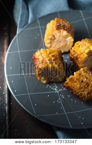 Slices of roasted corn on the gray plate closeup vertical
