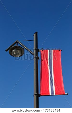 Norwegian banner hoisted in a lamp post on blue sky.