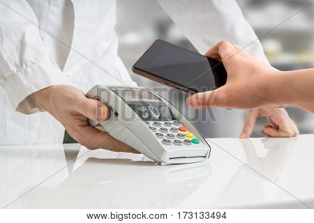 Customer is paying with smartphone using NFC technology in pharmacy