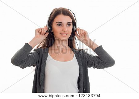 young lovely business woman in uniform with headphones and microphone looking away and smiling isolated on white