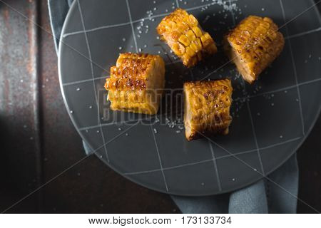 Slices of roasted corn on ceramic plate top view horizontal
