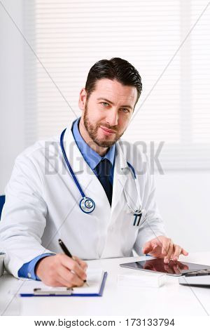 Doctor At Table Glancing At Camera