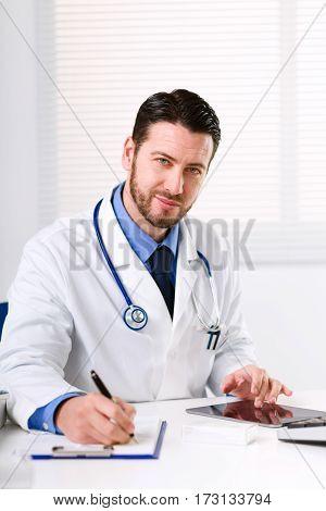 Doctor At Table Glancing At Camera