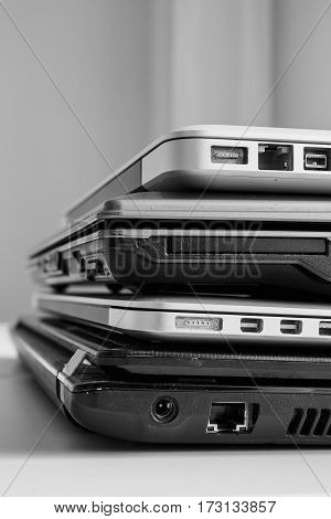 The different laptops placed on a table on a roll. Vertical indoors shot.