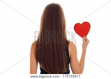 backside portrait of brunette woman in black dress and heart in hands isolated on white