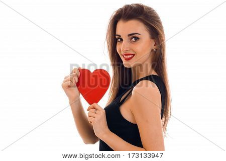 young pretty brunette woman in stylish black dress with red heart in her hands looking at the camera and smiling isolated on white