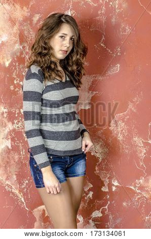 Young girl in denim shorts and a striped jacket