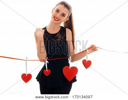 young pretty brunette woman in stylish black dress with red heart in studio looking at the camera and smiling isolated on white