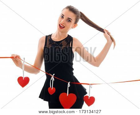 young charming brunette woman in stylish black dress with red heart in studio looking at the camera and smiling isolated on white