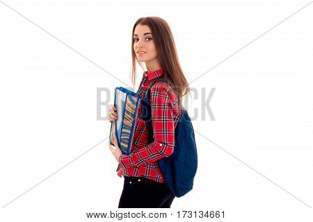 stylish beautiful brunette student girl with blue backpack and folder for notebooks in her hands looking at the camera isolated on white