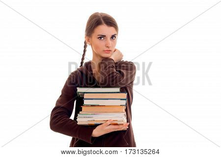 stylish serious brunette student girl with pigtails in brown sports clothes with books in her hands looking at the camera isolated on white