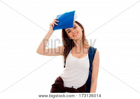 stylish cheerful brunette student girl with blue backpack and folder for notebooks in her hands looking and smiling on camera isolated on white
